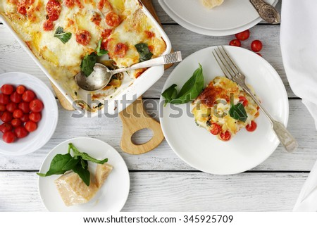 tasty lasagna with spinach on table - stock photo