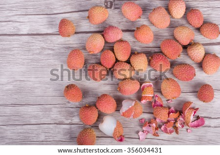 Tasty litchi exotic fruits on wooden background. Free space for your text. - stock photo