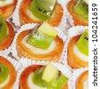Tasty little tarts with kiwi fruit, arranged in row. - stock photo