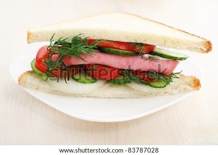 Tasty looking sandwich with ham and on a white plate. - stock photo