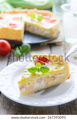 Tasty lunch - quiche with ham, tomatoes and zucchini - stock photo