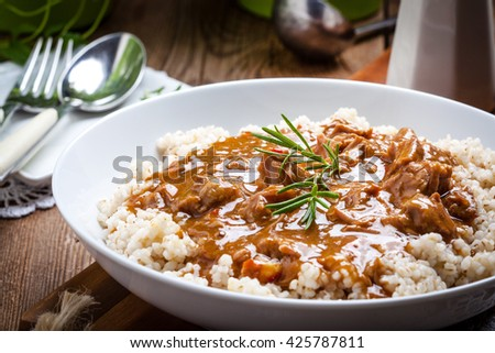 Tasty meal - cooked barley porridge and stew of pork. - stock photo