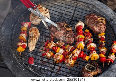 tasty meat and skewers on the barbecue outdoors - stock photo