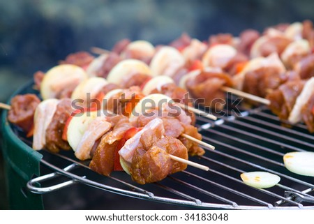 Tasty meat on grill in garden - stock photo