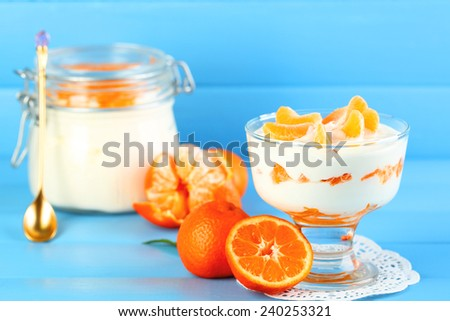 Tasty milk dessert with fresh tangerine pieces in glass bowl and jar, on color wooden background - stock photo