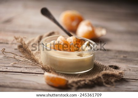 Tasty milk dessert with fresh tangerine pieces in glass bowl, on wooden background  - stock photo
