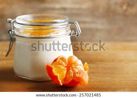 Tasty milk dessert with fresh tangerine pieces in glass jar, on  wooden background - stock photo