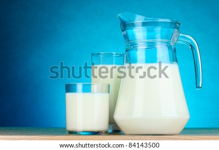 Tasty milk in jug and glasses on blue background - stock photo