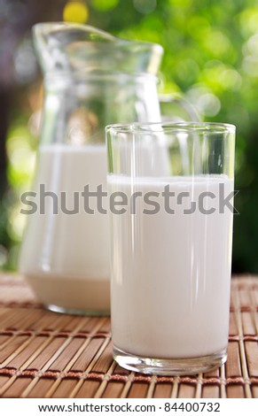 Tasty milk in jug and glasses on table
