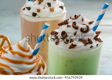 Tasty milkshakes in the foreground with blue and white straws. Seductive pieces of cookies and chocolate on the top with whipped topping. Organic drinks for healthy nutrition. - stock photo