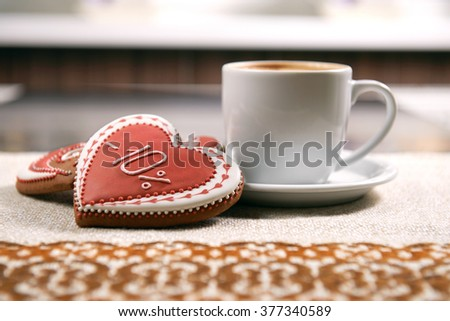 Tasty morning snack. Heart shaped decorated with glaze cookies served with a cup of warm cappuccino at the local coffee shop - stock photo