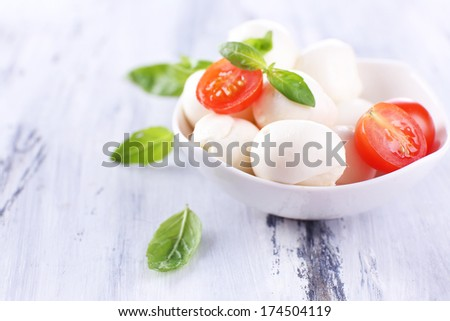 Tasty mozzarella cheese with basil and tomatoes in bowl, on wooden table - stock photo
