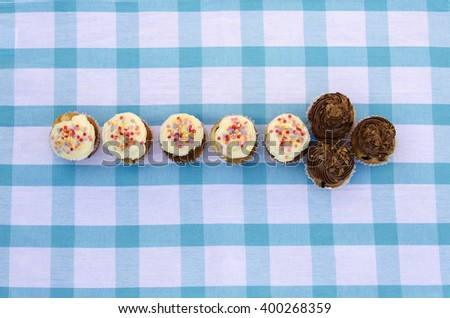 Tasty muffins with vanilla and chocolate cream decorated with sugar candy in a shape of an arrow - stock photo