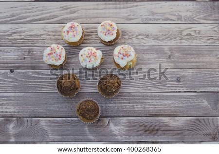 Tasty muffins with vanilla and chocolate cream decorated with sugar candy on a wooden background in a shape of a heart - stock photo