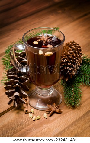 Tasty mulled wine with spices on a wooden table surrounded by fir branches - stock photo