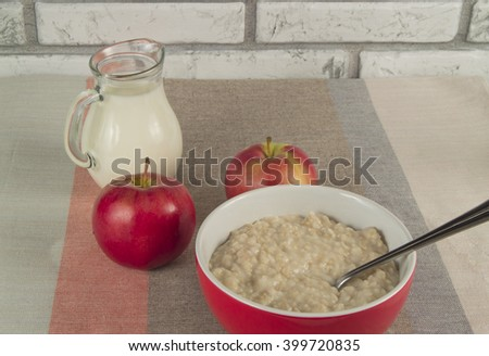 Tasty oatmeal with apples and  jug of milk. Healthy nutrition - stock photo