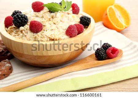 tasty oatmeal with berries and glass of juice, on wooden table