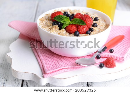 Tasty oatmeal with berries on table close-up - stock photo