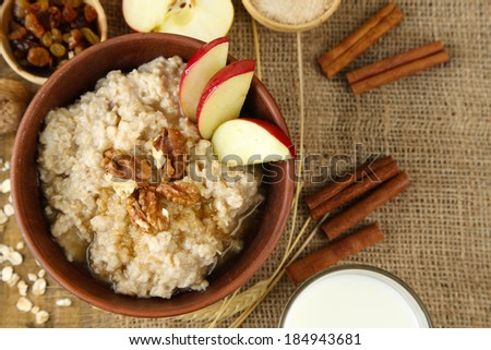 Tasty oatmeal with nuts and apples on table close up - stock photo