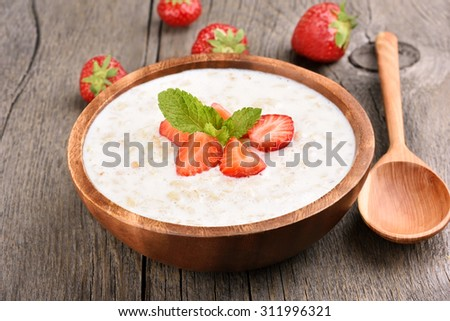 Tasty oatmeal with strawberry slices in bowl on rustic table