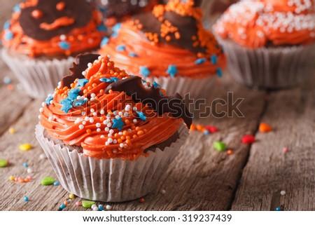 Tasty orange Halloween cupcakes with chocolate bat on a table close-up. horizontal - stock photo