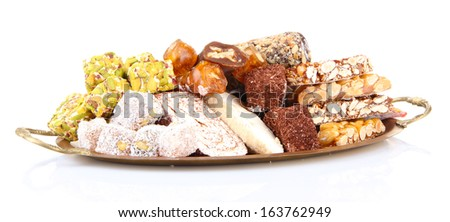 Tasty oriental sweets on metal tray, isolated on white - stock photo