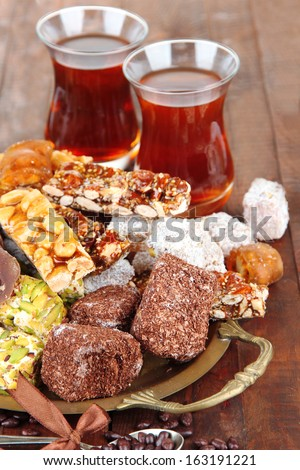 Tasty oriental sweets on tray and glasses of tea, on grey wooden background