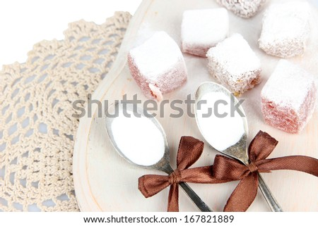 Tasty oriental sweets (Turkish delight) with powdered sugar, on  wooden desk - stock photo