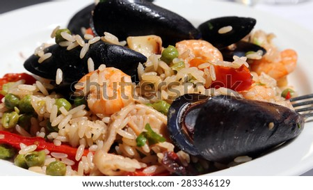 tasty paella rice dish with mussels, shrimp and green peas at fish restaurant