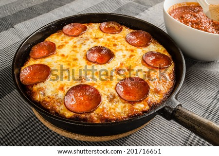 Tasty pan pizza with pepperoni salami and mozzarella in cast iron frying pan. - stock photo