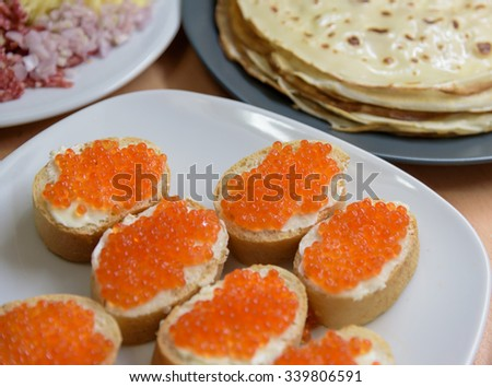 Tasty pancakes, sausage, cheese and sandwiches with red caviar - stock photo
