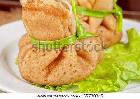tasty pancakes stuffed with meat served with lettuce and green onion