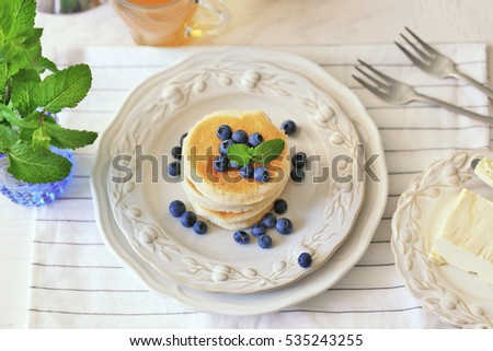 Tasty pancakes with blueberry on kitchen table