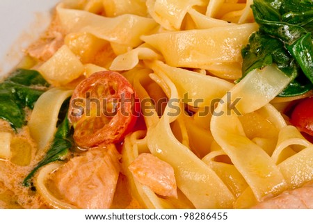 tasty pasta with cream, salmon, cheese and parsley close up - stock photo