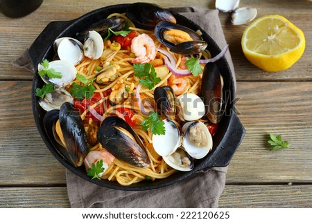 Tasty pasta with mussels, squid, parsley and lemon, top view - stock photo