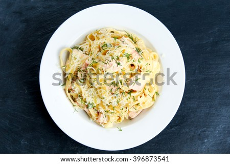 tasty pasta with salmon, dill on plate.  stone background - stock photo
