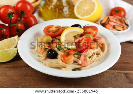 Tasty pasta with shrimps, mussels, black olives and tomato sauce on plate on wooden background - stock photo