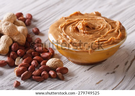 Tasty peanut butter in a bowl close up on the table. horizontal  - stock photo