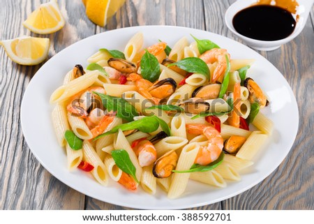 tasty penne pasta salad with shrimps, mussels and baby spinach leaves on a white dish, caramelized balsamic vinegar in a sauce boat and lemon slices on an rustic table, top view, selective focus - stock photo