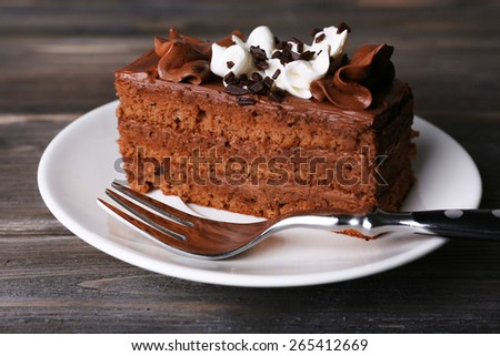Tasty piece of chocolate cake on wooden table background - stock photo