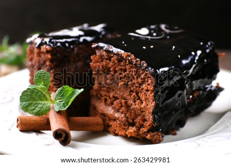 Tasty pieces of chocolate cake with mint and cinnamon on wooden table and dark background - stock photo