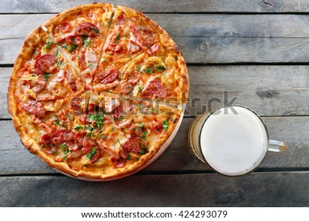 Tasty pizza and glass of beer are on wooden table, close up - stock photo