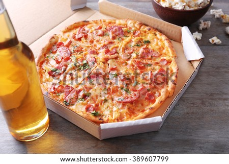 Tasty pizza in carton and bottle of beer are on wooden table, close up - stock photo