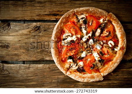 Tasty pizza on a wooden board .  - stock photo