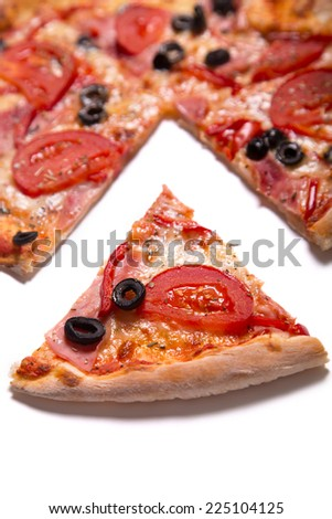 Tasty pizza with ham, tomatoes and olives with a slice removed, selective focus on slice   - stock photo