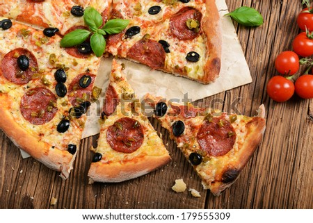 Tasty pizza with olives and salami - stock photo