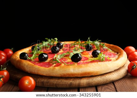 Tasty pizza with salami and olives decorated with tomatoes on wooden table against black background - stock photo