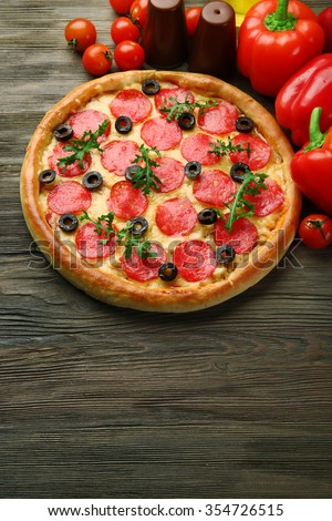 Tasty pizza with salami and red vegetables on wooden background, copy space