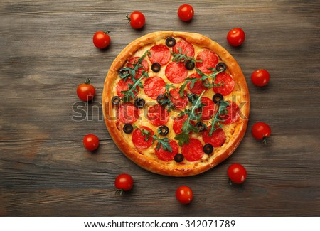 Tasty pizza with salami decorated with tomatoes on wooden background