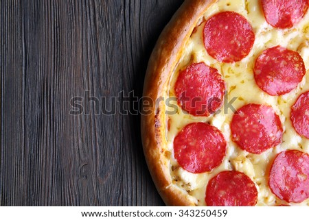 Tasty pizza with salami on wooden background, close up - stock photo